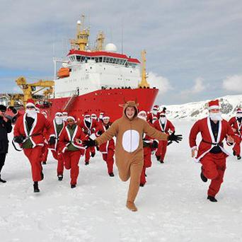 Members of HMS Protector's Ship's Company taking to the ice dressed as Santa Claus on Deception Island