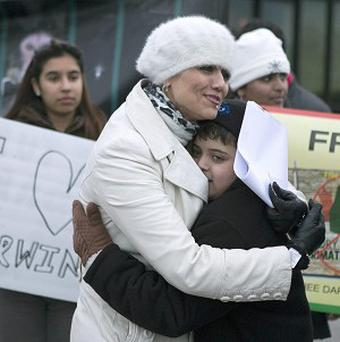 Yasmin Nakhuda, left, hugs her 12-year old son Misha outside an Animal Services offices in Toronto, Canada (AP/The Canadian Press, Chris Young)