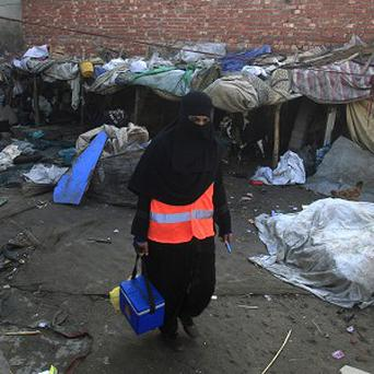 A Pakistani health worker visits Lahore's slums to administer the polio vaccine to infants (AP)