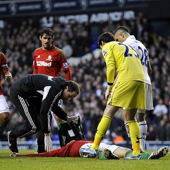 Michu, bottom, was floored following an aerial challenge with Spurs goalkeeper Hugo Lloris