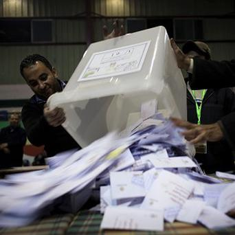 Election workers empty a ballot box at the end of the second round of a referendum on a disputed constitution (AP/Nasser Nasser)