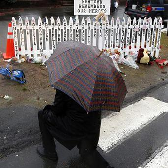 A man kneels in front of a makeshift memorial during a moment of silence in Newtown, Connecticut, to mark one week since the massacre.(AP)