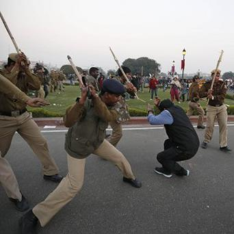 Indian policemen baton charge a protester as he is driven back from North Block near the Presidential Palace in New Delhi (AP)