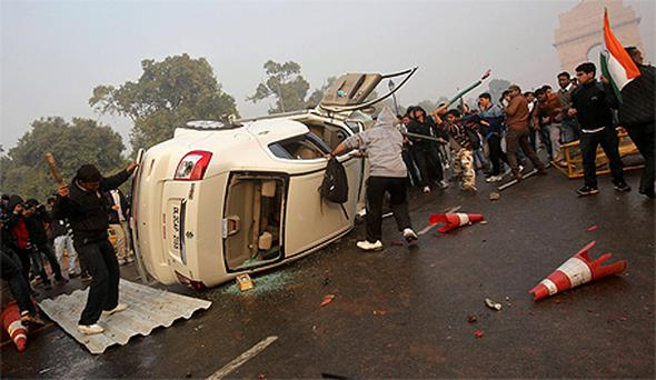 Demonstrators overturn a vehicle during a protest in New Delhi