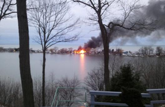 A fire burns on Lake Road after a suspect shot four firefighters responding to the blaze in Webster, New York, December 24, 2012. At least two upstate New York firefighters were shot and killed and two wounded on Monday at the scene of an early morning house fire in a suburb of Rochester, according to local news reports. REUTERS/WHEC/Christine VanTimmeren/Handout (UNITED STATES - Tags: CRIME LAW) NO SALES. NO ARCHIVES. FOR EDITORIAL USE ONLY. NOT FOR SALE FOR MARKETING OR ADVERTISING CAMPAIGNS. THIS IMAGE HAS BEEN SUPPLIED BY A THIRD PARTY. IT IS DISTRIBUTED, EXACTLY AS RECEIVED BY REUTERS, AS A SERVICE TO CLIENTS