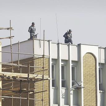 Afghan policemen stationed on top of Kabul police headquarters following the killing of an American adviser (AP)