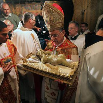 Latin Patriarch of Jerusalem Fouad Twal holds the Baby Jesus during a ceremony at the Church of the Nativity, in Bethlehem (AP)