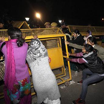 Indian women protesting against the brutal gang-rape of a woman on a moving bus try to remove police barricades in New Delhi (AP)