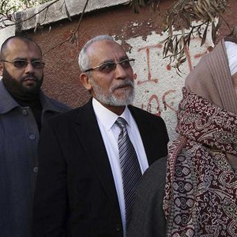 Muslim Brotherhood leader Mohammed Badie waits outside a polling place in Beni Suef to vote in the referendum on an Egyptian constitution (AP)