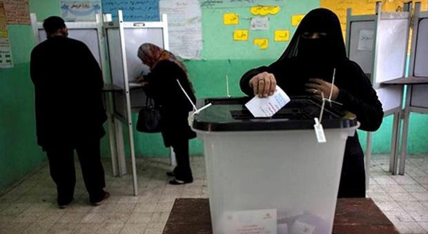 A veiled Egyptian woman casts her vote at a polling station in the second round of a referendum on a disputed constitution drafted by Islamist supporters of president Mohammed Morsi, in Giza, Egypt.