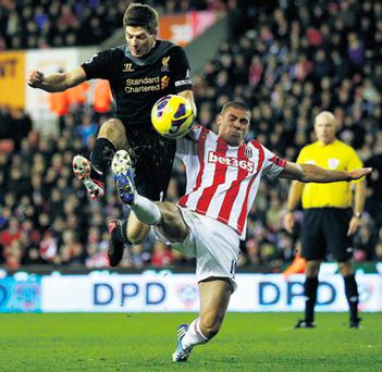 Two-goal hero Jonathan Walters challenges Steven Gerrard during Stoke's victory against Liverpool
