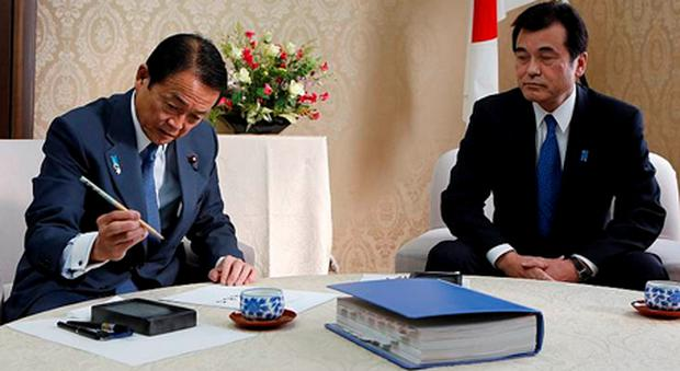 Japan's new Finance Minister Taro Aso (left) prepares to sign his name with a calligraphy brush on a document to mark the transfer of duties as former Finance Minister Koriki Jojima looks on at the Finance Ministry in Tokyo.
