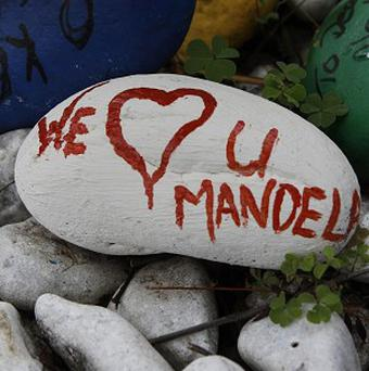 A pebble with a message to former South Africa president Nelson Mandela lays outside his Johannesburg home (AP)