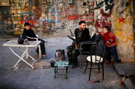A Free Syrian Army fighter jokes with a child in the old city of Aleppo. Photo: Reuters