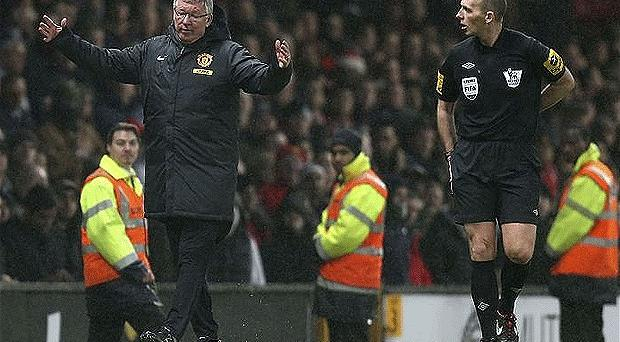Let's talk: Manchester United's Sir Alex Ferguson complains to referee Mike Dean about a Jonny Evans own-goal that was allowed to stand for Newcastle. Photo: Getty Images