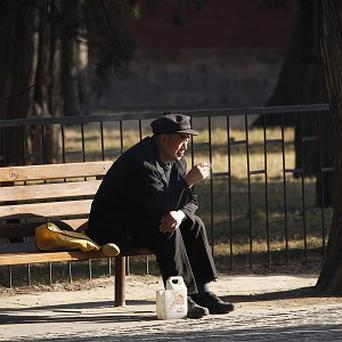 An elderly Chinese man sits alone at a park in central Beijing. Under a new law, his children would be forced to visit him (AP)