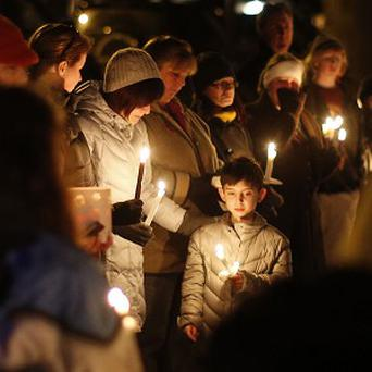 Mourners in Newtown, Connecticut hold a candlelight vigil for the Sandy Hook shooting victims (AP)