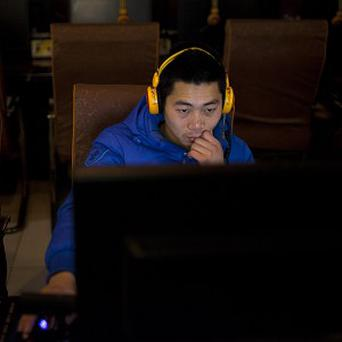 A man uses a computer at an internet cafe in central Beijing (AP)