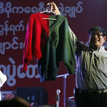 Presenters show a sweater hand-knitted by Aung San Suu Kyi during an auction (AP)