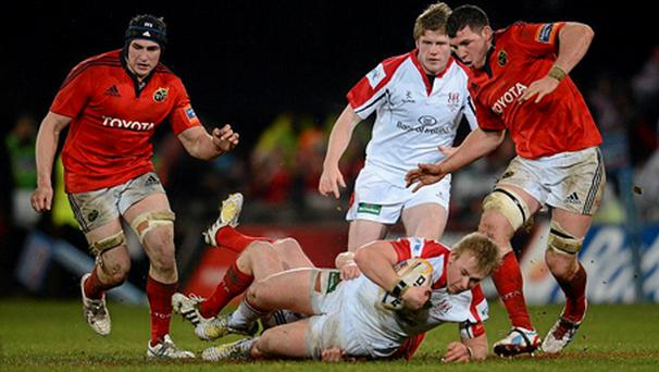 Luke Marshall, Ulster, is tackled by Munster's Ronan O'Gara.