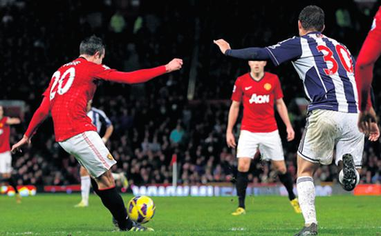 Manchester United striker Robin van Persie shoots to score his side's second goal in the win over West Brom at Old Trafford.