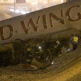 Rescuers work at the site where a plane careered off the runway at Vnukovo Airport in Moscow, Russia (AP)