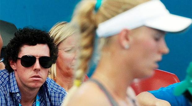 Rory McIlroy watches as girlfriend Caroline Wozniacki plays Ksenia Pervak of Kazakhstan during their women's singles match at the Brisbane International tennis tournament. Photo: Reuters