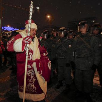 A festive Muscovite passes police lines during a protest (AP)