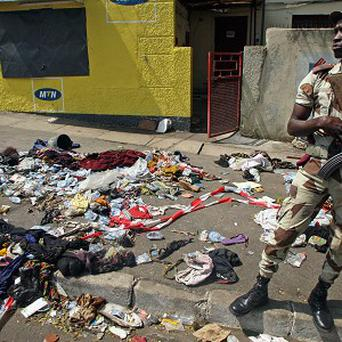 An Ivory Coast troop stands next to the belongings of people involved in a deadly stampede in Abidjan, Ivory Coast (AP)