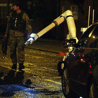 An Army bomb disposal expert moves in to examine a booby trap bomb found under a policeman's car in Belfast
