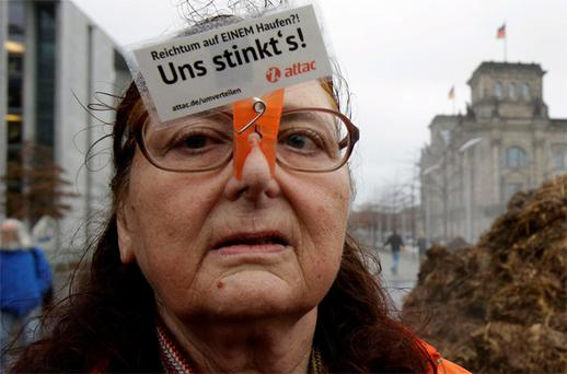 A demonstrator for social fairness in Berlin wears a sign that reads: 'Richness on one pile?! We are fed up!'