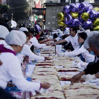 In a Three Kings Day pre-celebration, city employees serve slices of a mile- long Rosca de Reyes in Mexico City (AP/Eduardo Verdugo)