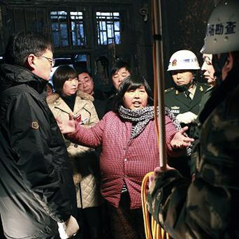 Yuan Lihai, center, speaks to investigators at the burnt remains of her private shelter for orphans and abandoned children in Lankao (AP)