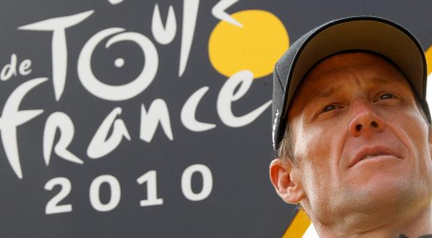 Radioshack team rider Lance Armstrong of the U.S. poses on the podium in Paris after the final 20th stage of the 97th Tour de France cycling race between Longjumeau and Paris in this July 25, 2010, file photo. REUTERS/Eric Gaillard/Files (FRANCESPORT DAY - Tags: SPORT CYCLING)