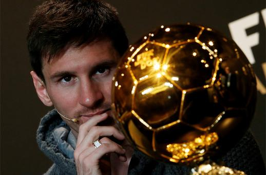 Lionel Messi of Argentina watches the trophy during a news conference before the FIFA Ballon d'Or 2012 soccer awards ceremony