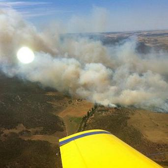 Plumes of smoke rise from a fire near Cooma, Australia (AP/New South Wales Rural Fire Service)