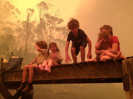 Photo provided by the Holmes family, the Walker siblings six-year-old Caleb, left, four-year-old Esther, second from left, nine-year-old Liam, and eleven-year-old Matilda, right, holding two-year-old Charlotte, prepare to enter the water to take refuge with their grandparents under a jetty as a wildfire rages nearby in the Tasmanian town of Dunalley, east of the state capital of Hobart, Australia. Photo: AP