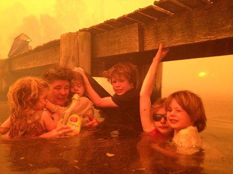 Tammy Holmes and her grandchildren take refuge under a jetty as a wildfire rages near-by in the Tasmanian town of Dunalley. Photo: AP