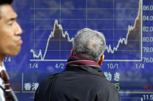 A man looks at an electronic stock board of a securities firm in Tokyo, Thursday. A positive start to US corporate earnings season helped boost Asian stock markets Thursday. Photo: AP