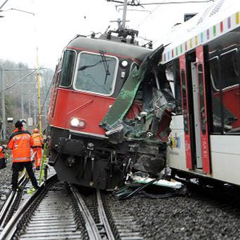 Rescuers and police stand next to two passenger trains that collided near the station of Neuhausen in northern Switzerland (AP/Keystone)