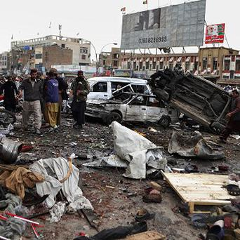 Pakistani police officers and local residents gather at the site of bomb blast in Quetta (AP)