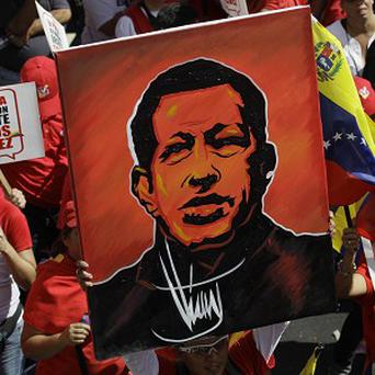 A supporter of Venezuela's President Hugo Chavez holds up a painting of him during a symbolic inauguration rally in Caracas (AP)