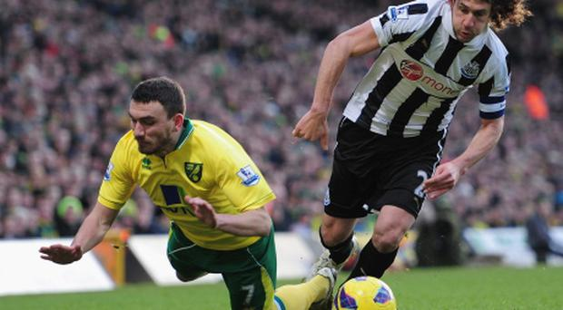 NORWICH, ENGLAND - JANUARY 12: Fabricio Coloccini of Newcastle United battles with Robert Snodgrass of Norwich City during the Barclays Premier League match between Norwich City and Newcastle United at Carrow Road on January 12, 2013 in Norwich, England. (Photo by Jamie McDonald/Getty Images)