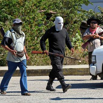 Civilians wearing ski masks or bandanas and carrying small arms in Mexico are arresting people suspected of crimes and imposing a curfew (AP)