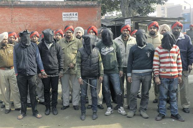 Indian policemen guard six men, their faces covered, suspected of raping a bus passenger in Punjab state. Photo: AP