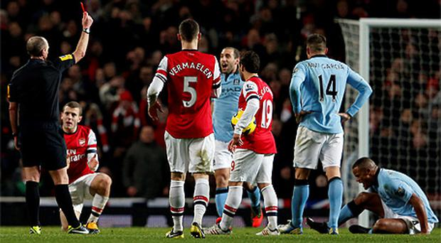 Mike Dean shows Vincent Kompany the red card