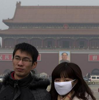 A woman wears a mask in Beijing amid high pollution (AP)