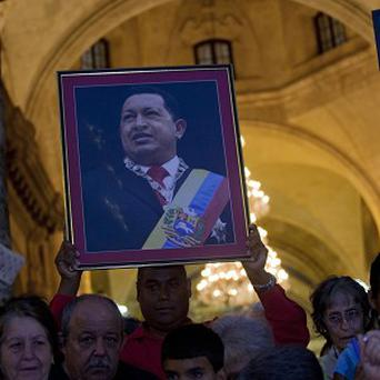 A man holds a framed image of Hugo Chavez after attending a mass to pray for the president (AP)