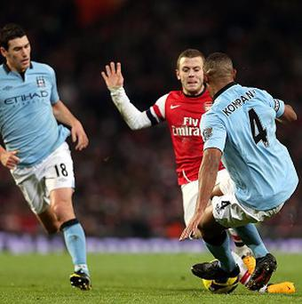 Vincent Kompany, right, challenges Jack Wilshere