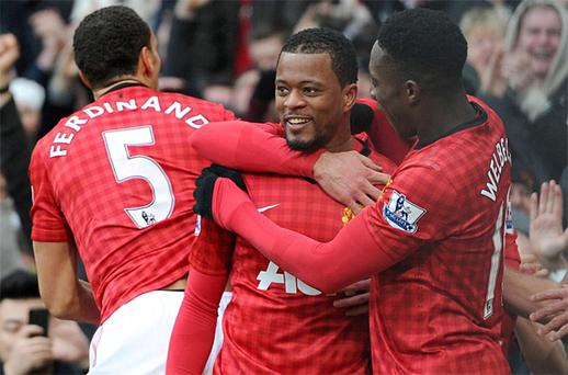 Patrice Evra celebrates scoring against Liverpool with teammates Rio Ferdinand (left) and Danny Welbeck